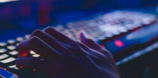 Person spiller computer med et tastatur med lys i
