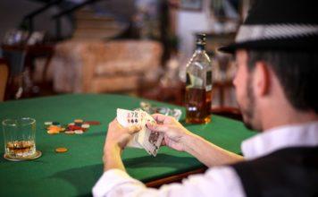 Mand spiller poker på bar med whiskey ved siden